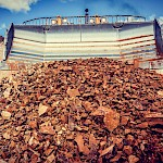 The wide blade of a bulldozer pushes together a large pile of ore that will be transported to the Crusher and then to the Heap Leach Pad for processing at the Moss Mine.