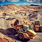 All working together; a CAT front-end loader loads an articulated truck.  The various pieces of equipment work together to excavate & haul ore.  Each executing a vital step towards the mining, crushing, leaching and pouring of gold at the Moss Mine.